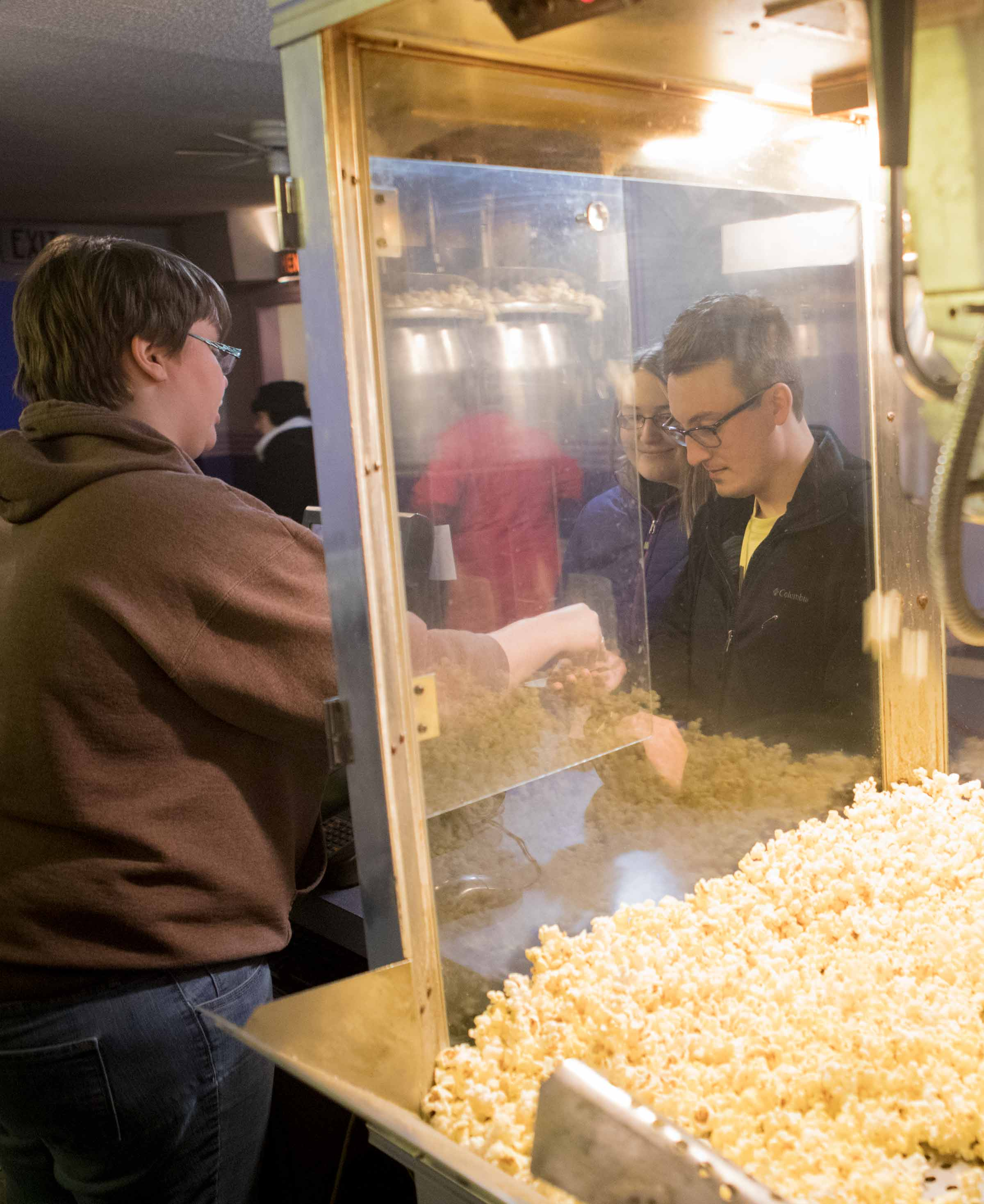 "Fifth-year pharmacy student Caitlin Nahirniak and Andy Kremyar, a 2015 Ohio Northern University graduate, buy concessions before the start of a free screening of the movie ""Friday Night Lights"" at Ada Theatre."
