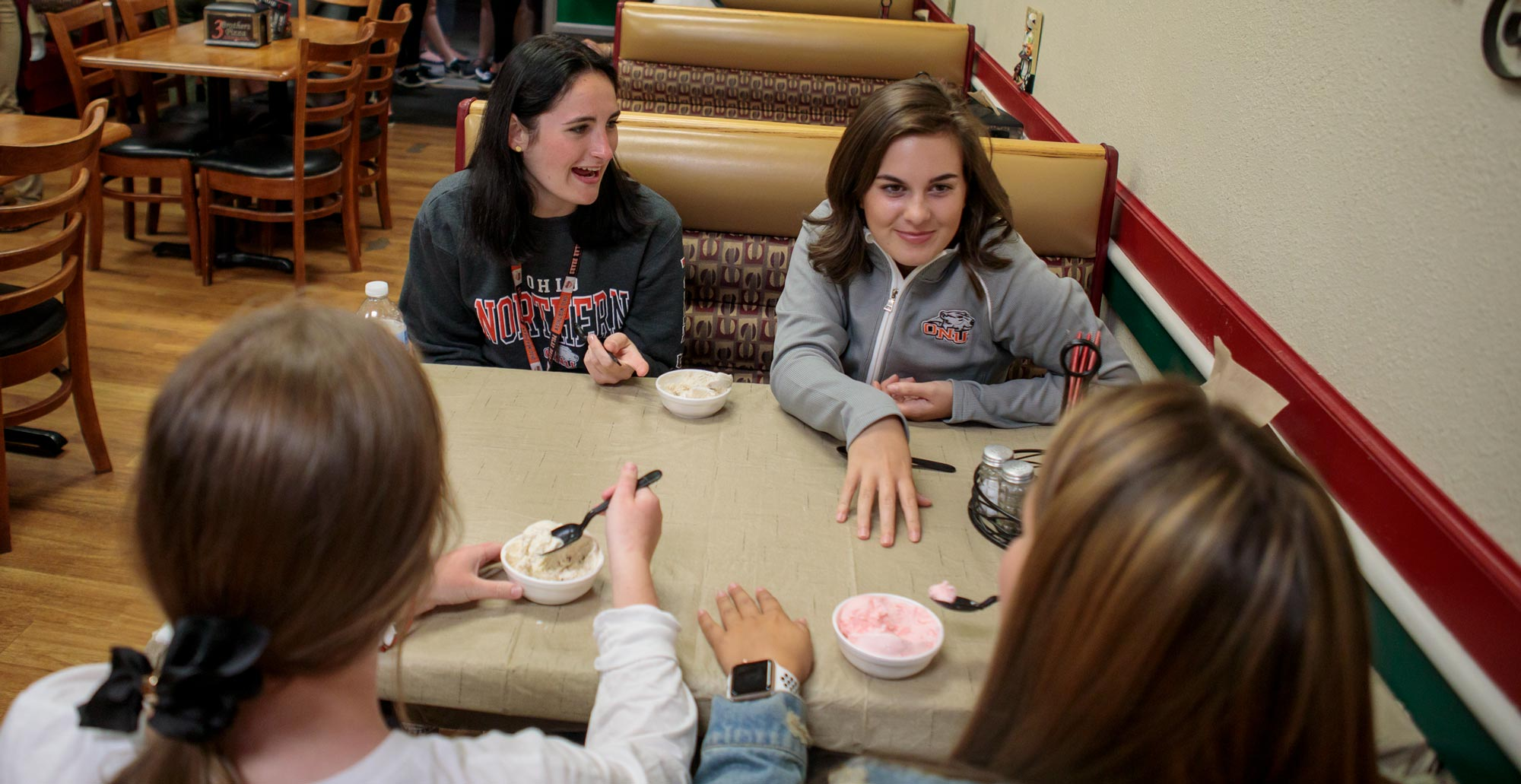 From left, first-year pharmacy student Denise Williams and freshman Isabella Orofino talk and eat ice cream at Three Brothers Pizza.