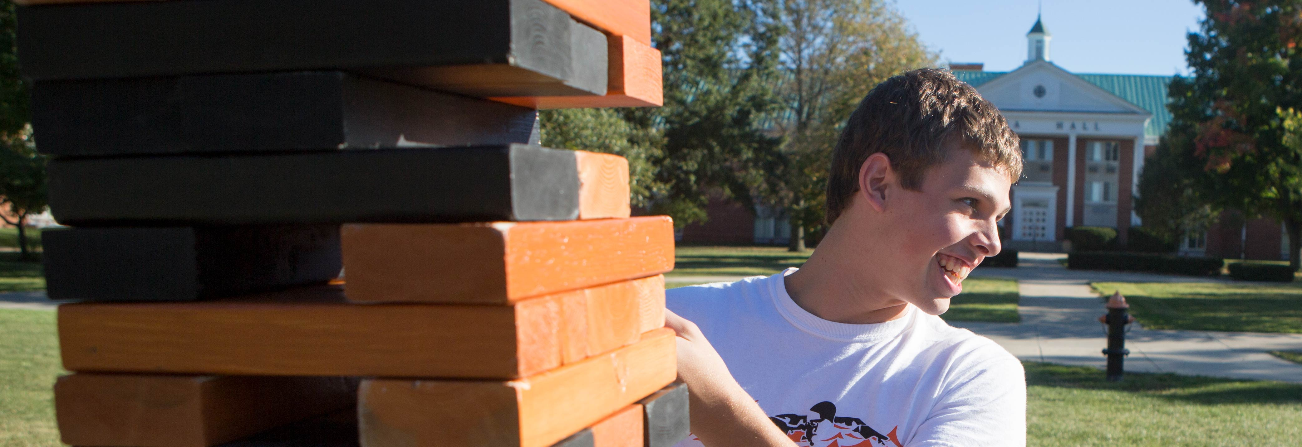 Student plays Jenga outside Lima Hall