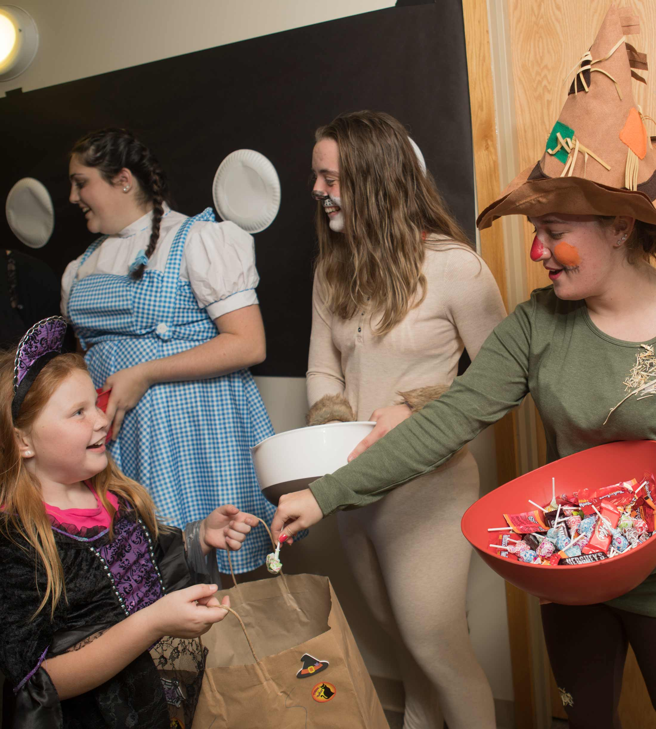 Students pass out candy to kids in Affinity West during Trick-or-Treat night