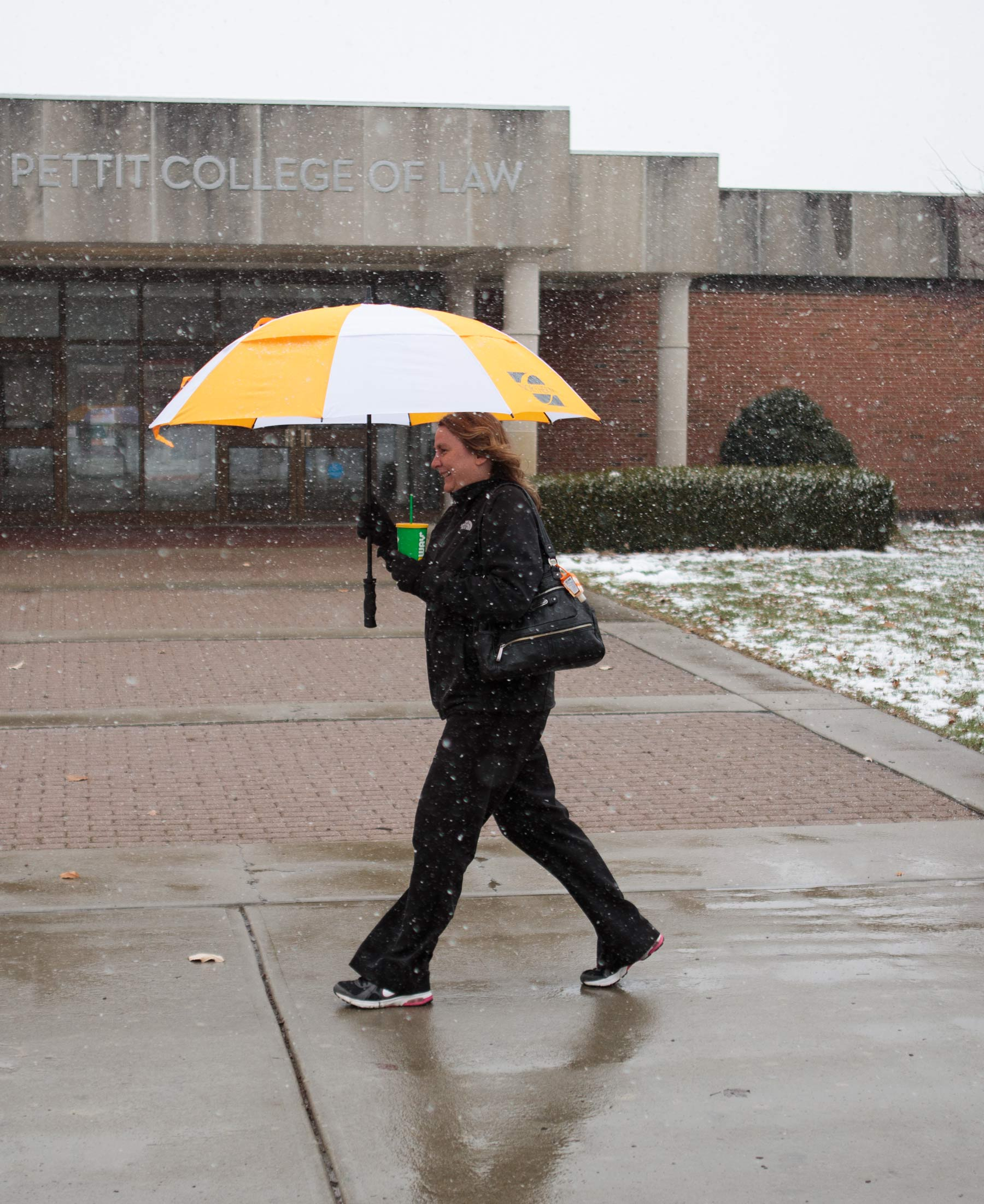 Deb Miller, director of admissions, walks under an umbrella through the snow
