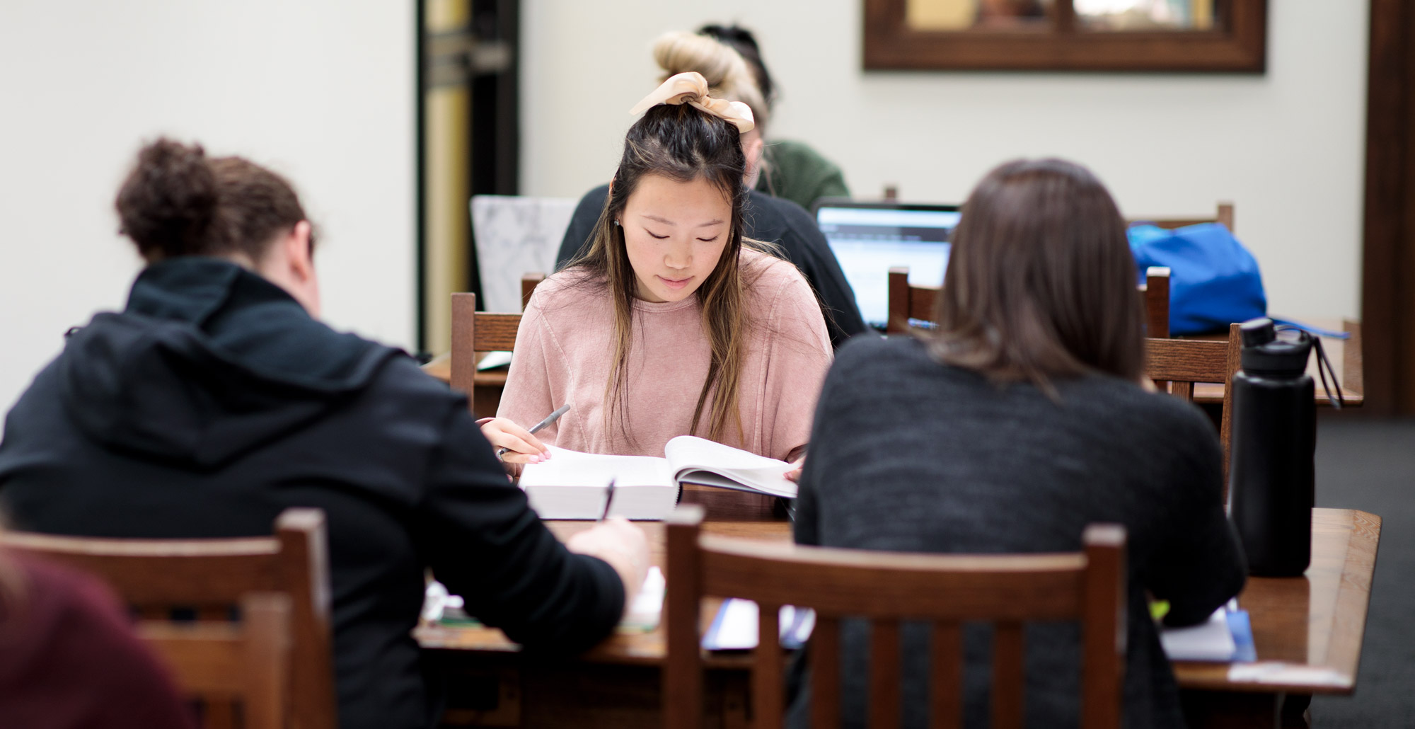 Student studies with peers in the library.