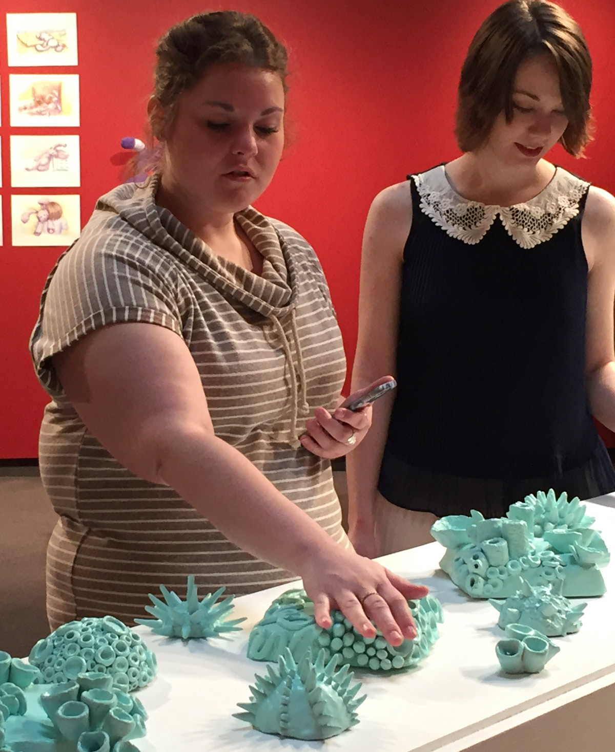 student touching a ceramics display at a gallery opening.