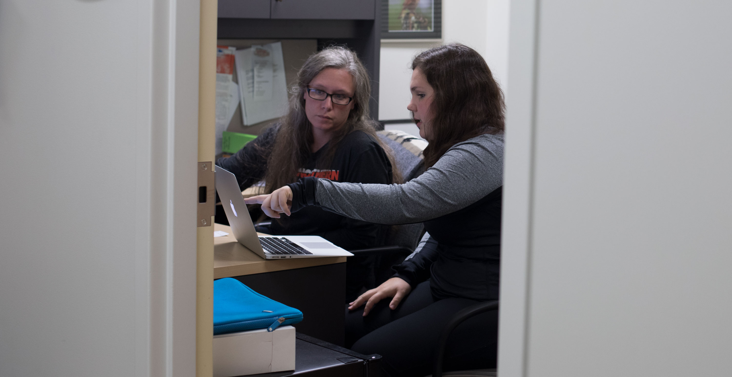 Biology professor helping student in her office.
