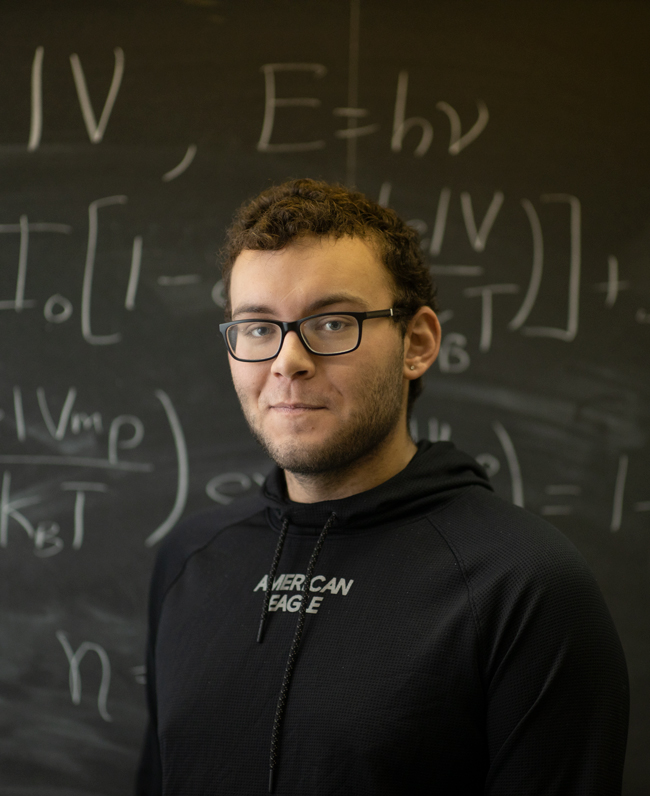 physics student pictured in front of a chalkboard.