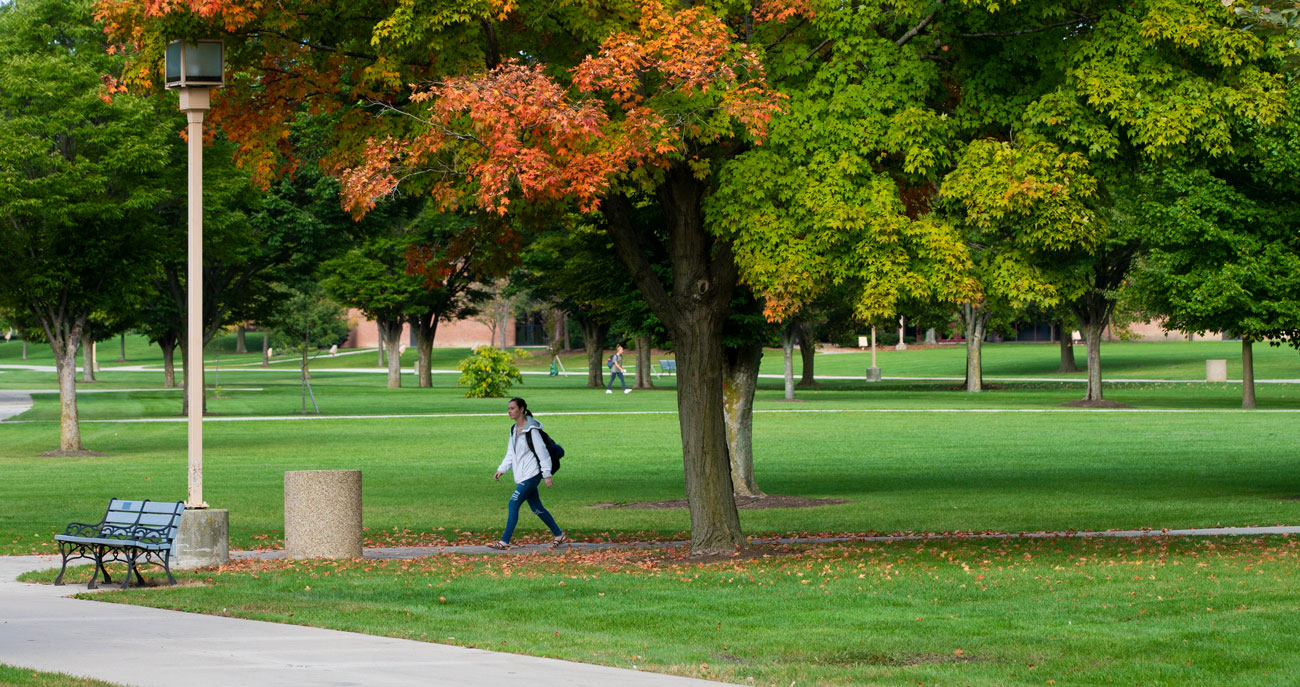 student walking across campus during the fall.